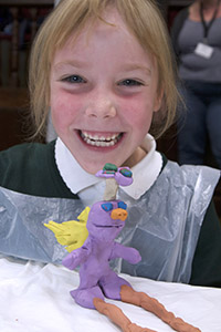 A happy child with their flying creature plasticine model